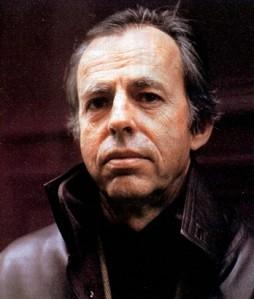 Photo de Bernard portant un manteau brun foncé, regardant la caméra. Les tons de couleurs et son manteau donnent une ambiance chaleureuse.
